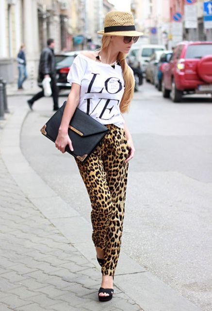 Modelo usa calça estampada, camiseta estampada, chapeu feminino e sandalia meia pata preta com bolsa carteira na mesma cor.