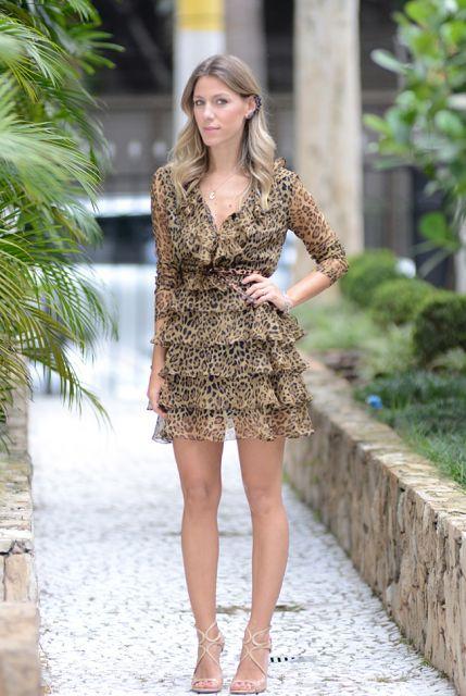 Modelo usa vestido com estampa de oncinha curto, meia manga com sandalia nude.