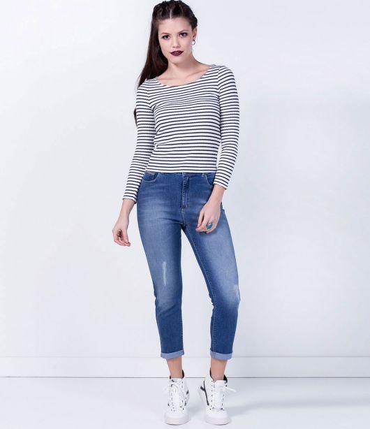 Modelo usa calça jeans, blusa sueter cinza e tenis branco.