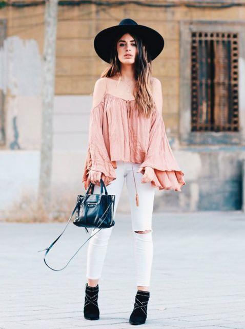 Modelo usa calça branca rasgada no joelho, blusa rosa, chapeu, bolsa e bota preta.