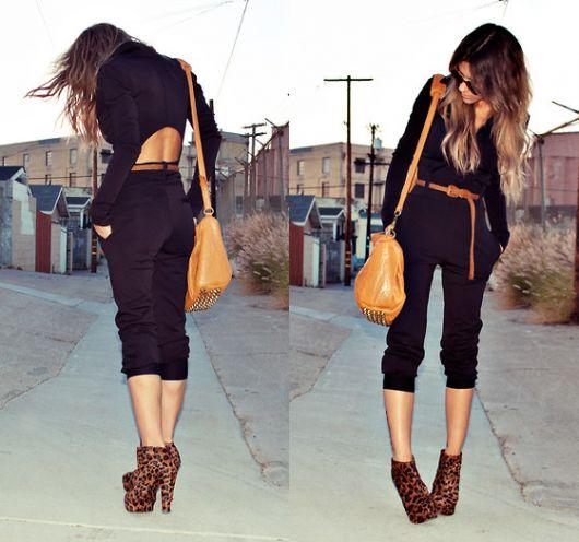 Modelo usa calça capri preta, blusa preta e ankle boot animal print.