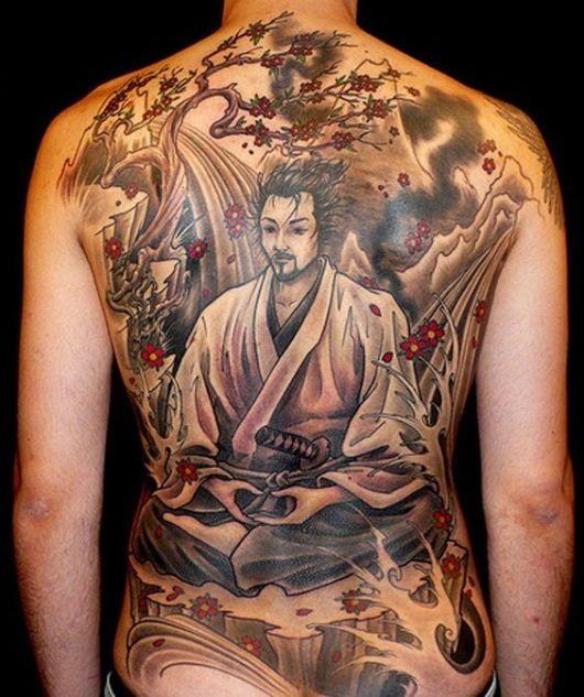Tatuagem de um samurai meditando. Ele está com um roupão branco e sem máscaras. Ao fundo há uma cerejeira cujas folhas vermelhas estão sendo levadas pelo vento.