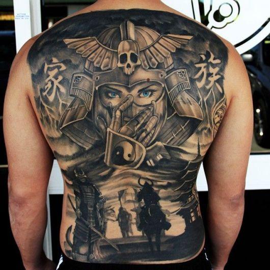 Tatuagem cobrindo as costas inteira. Nela há o rosto grande um samurai e mais abaixo a sombra de outros samurais menores, alguns a pé e outros a cavalo.