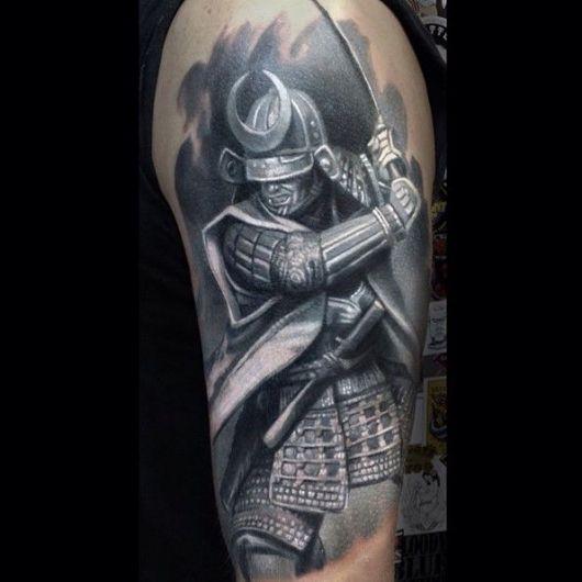 Tatuagem de um samurai completamente coberto por sua armadura empunhando uma espada em posição de ataque