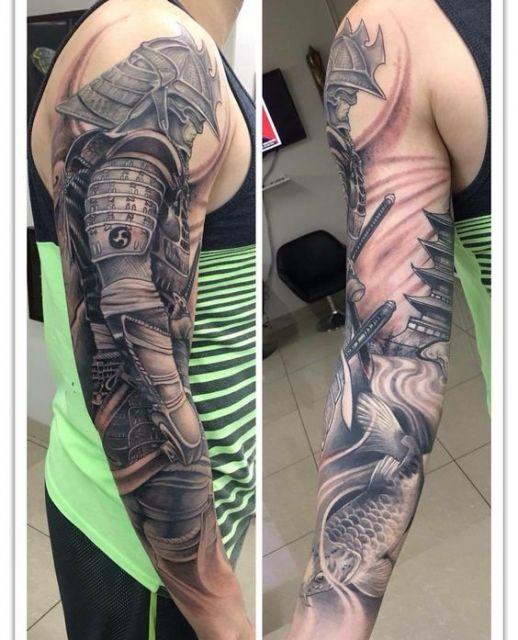 Tatuagem de um samurai cobrindo o braço inteiro de um homem. Ele está com sua armadura completa e ao fundo pode ser observado um templo japones.