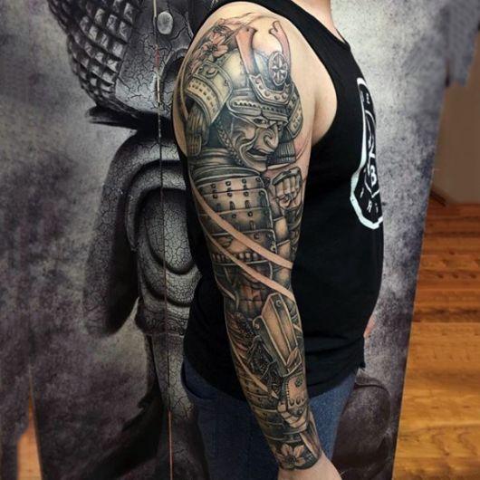 Tatuagem de um samurai cobrindo o braço inteiro de um homem. Ele está com uma armadura muito poderosa e seu rosto é coberto por uma máscara e chapéu.