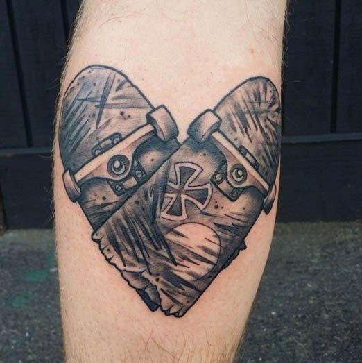 Tatuagem simples de dois shapes partidos ao meio formando um coração. O shape da frente tem um sol e uma cruz desenhados nele.