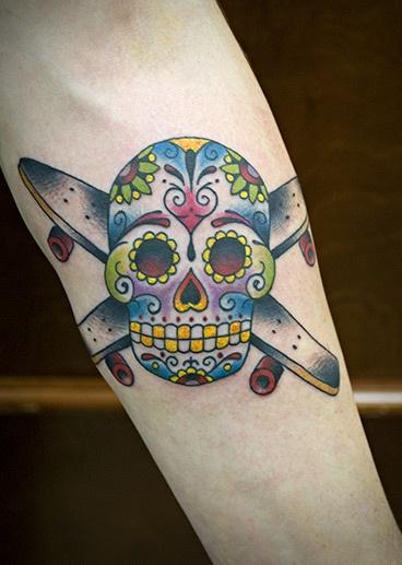 Tatuagem de dois skates cruzados e uma caveira mexicana colorida na frente dos dois.