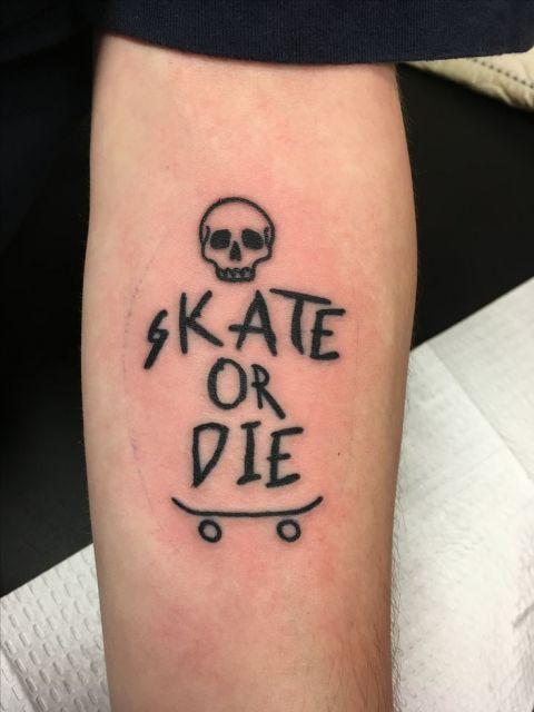 """Tatuagem do contorno de um skate com e uma caveira. Entre eles há a frase """"Skate or Die""""."""