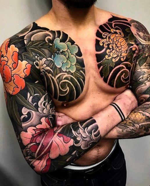 Homem com os braços cruzados. Sua tatuagem cobre os braços inteiros e parte do peito.