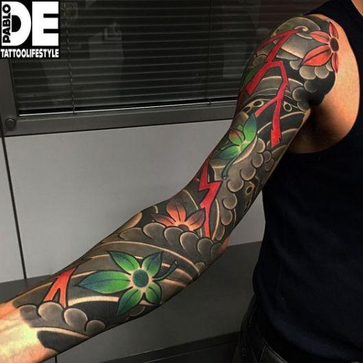 Tatuagem cobrindo o braço de um homem que utiliza muito o preto contrastando com as cores vivas de pequenas folhas