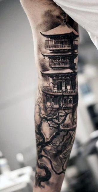Tatuagem no braço feita com sombreamento de um castelo oriental com uma árvore seca na frente