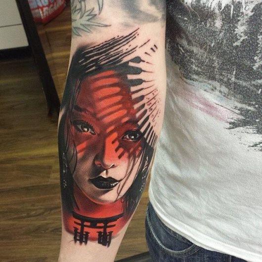 Tatuagem no braço de uma gueixa com o rosto pintado de vermelho por causa do reflexo do sol