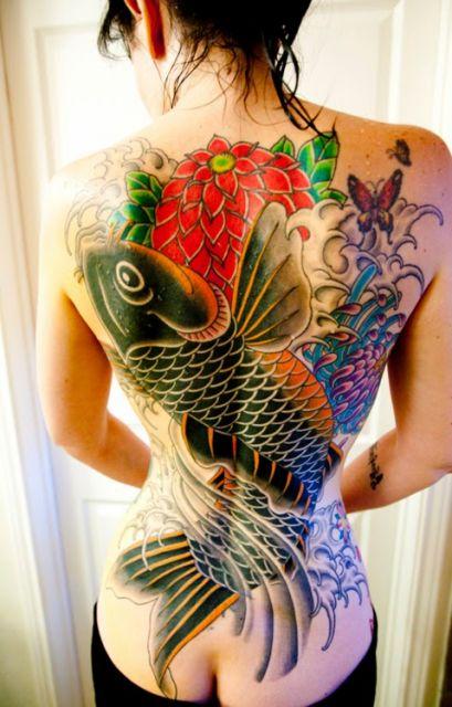 Tatuagem cobrindo completamente as costas de uma mulher de uma carpa pintada de preto e laranja