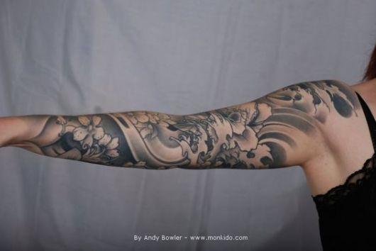 Braço de uma mulher estendido horizontalmente com uma tatuagem oriental de diversas flores feitas com sombreamento