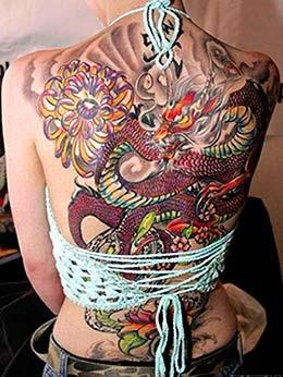 Tatuagem de um dragão oriental colorido cobrindo as costas de uma mulher