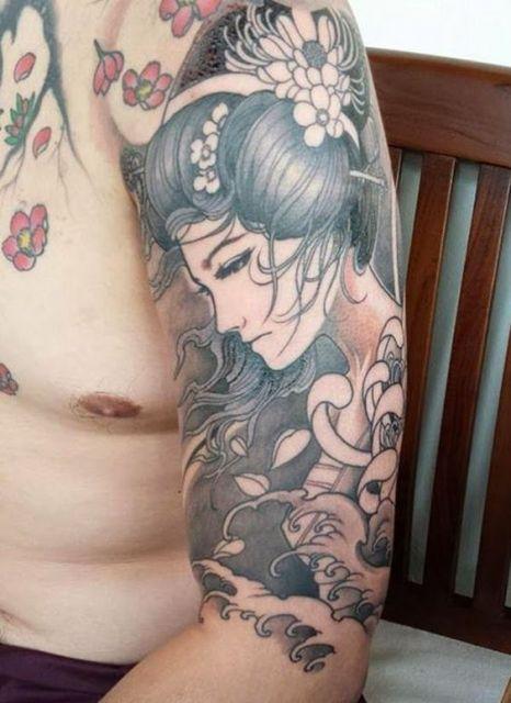 Tatuagem no braço de uma gueixa de perfil olhando para baixo com expressão de tristeza
