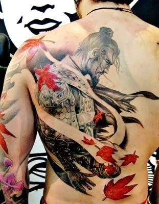 Tatuagem nas costas de um samurai sem capacete com folhas vermelhas caindo ao seu redor.