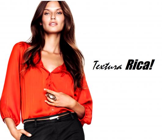 Modelo usa calça preta social e camisa de seda laranja.