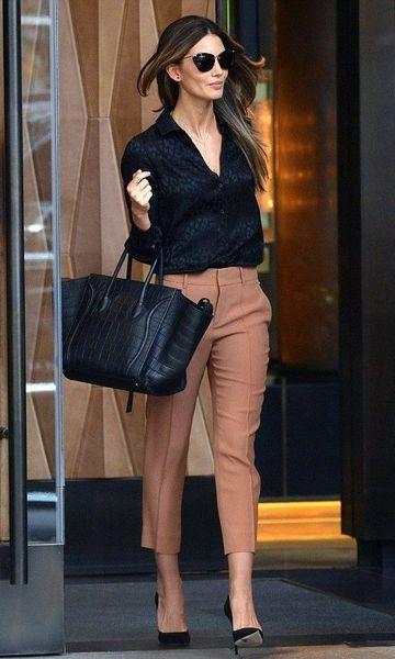 Modelo veste calça de alfaiataria caramelo, camisa preta, sapato social preto e bolsa no mesmo tom.