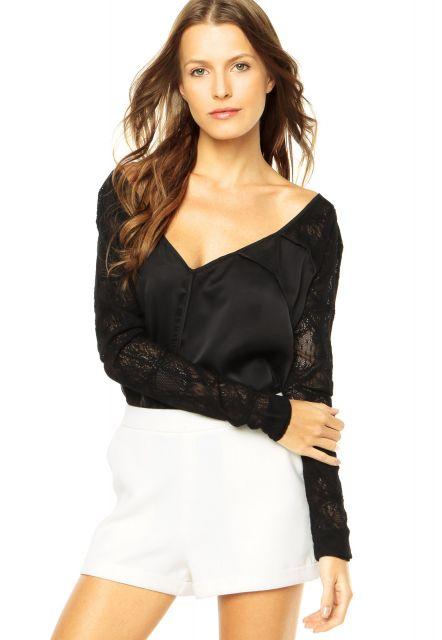Modelo usa blusa preta em seda com saia branca.