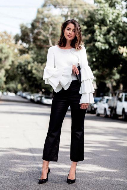 Modelo veste calça preta cigarrete, blusa manga longa branca de seda com babados nas mangas.