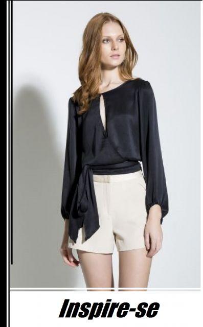 4d37749ef Modelo usa bermuda branca e blusinha preta manga longa de seda com decote  aberto.