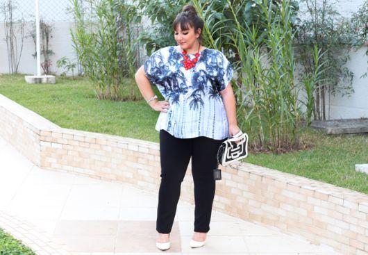 Modelo usa calça preta, blusa de seda estampada em tons de azul, scarpin branco e colar vermelho.