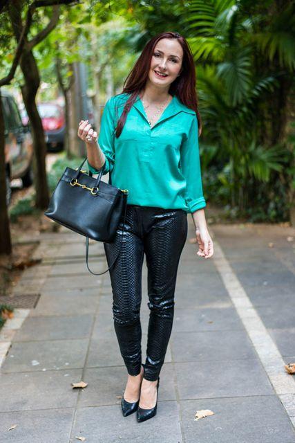 Modelo usa calça de couro, blusa verde clara, bolsa preta e sapato preto.