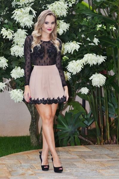 Modelo usa saia rosê com preto, body transparente e sapato preto.