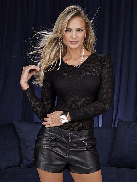 Modelo usa short preto de couro e body transparente de renda.