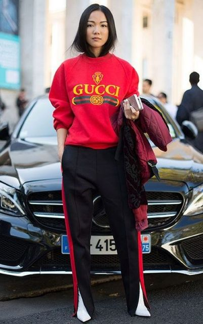 Modelo usa moletom gucci vermelho, calça preta com vermelho e bota branca.