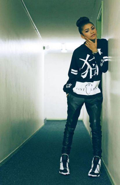 Modelo usa calça de couro preta, moletom preto e brancoe e tenis na mesma cor.