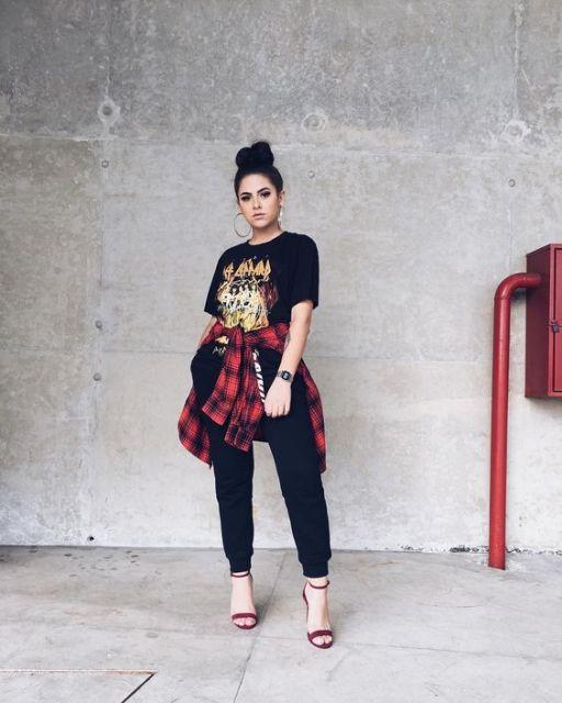 Modelo usa camiseta estampada preta, calça moletom, camisa xadrez e sandalia vermelha.
