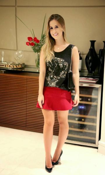 Modelo usa saia vermelha, blusa regata preta estampada e sapato preto.