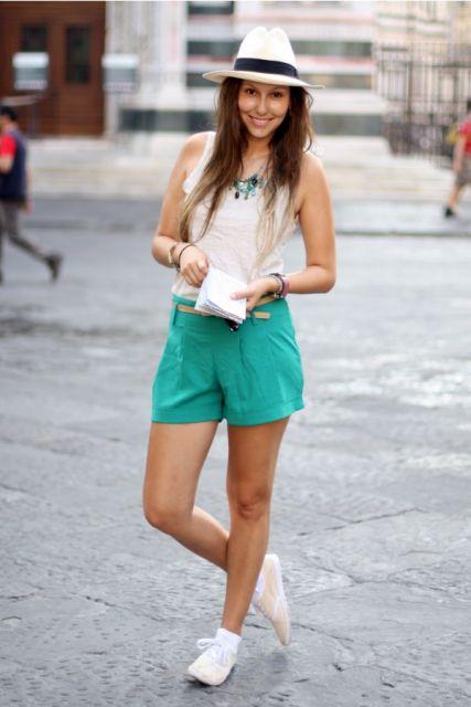 Modelo usa short verde, regata branca e tenis branco.