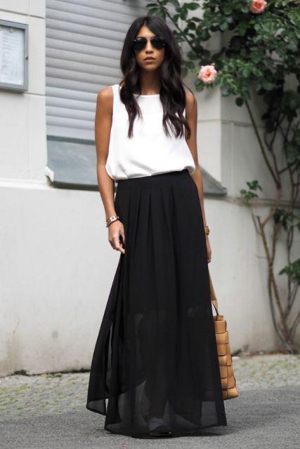 Modelo usa saia longa preta e blusa regata branca.