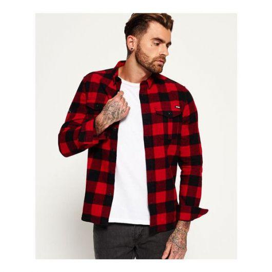83edadc7f45a0 Foto de um homem tatuado usando uma camisa vermelha xadrez aberta com uma  camiseta branca simples