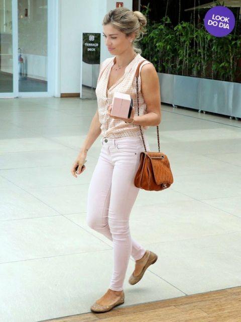 Grazi Massafera usa regata rose, calça jeans branca e sapatilha com bolsa caramelo.