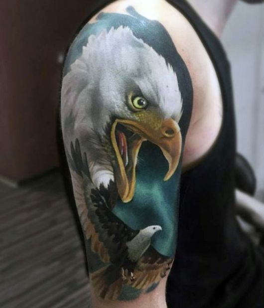 Tatuagem que vai do topo do ombro até metade do braço com o rosto de uma águia real de bico aberto e uma outra águia menor voando