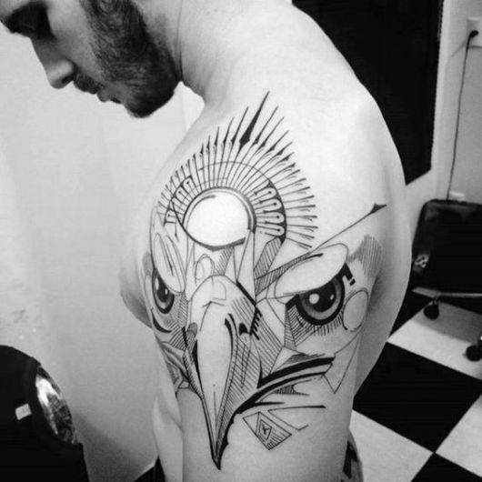Tatuagem abstrata dos traços do rosto de uma águia feita no ombro de um homem