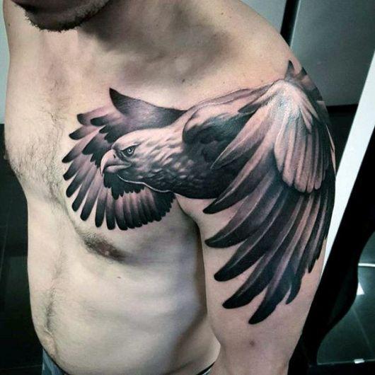 Tatuagem no ombro e parte do peito de um homem com o desenho de uma águia voando com as asas muito grandes
