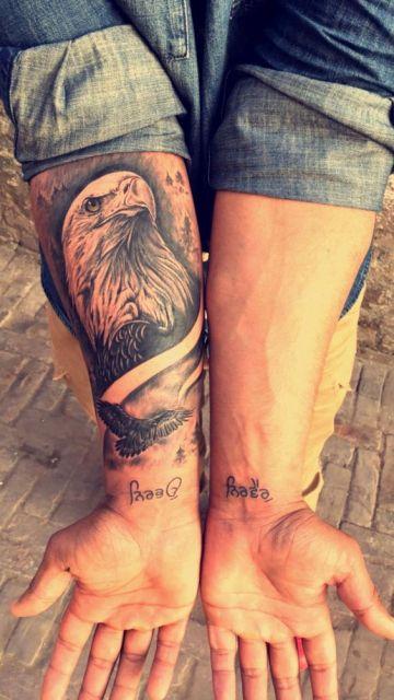 Tatuagem no antebraço com o desenho da cabeça de uma águia real olhando para o horizonte