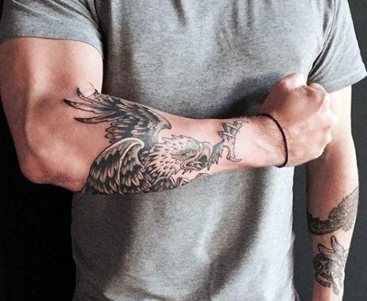 Tatuagem no antebraço com o desenho de uma águia real no estilo tradicional pronta para atacar