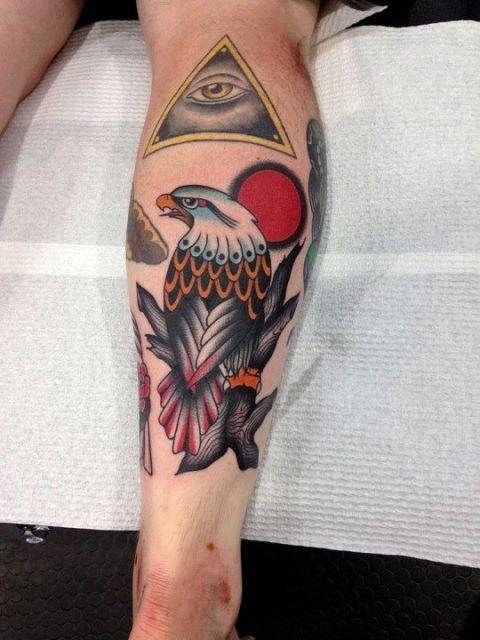 Tatuagem na panturrilha de uma águia vista de costas feita com cores vivas como vermelho e laranja