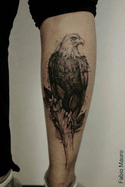 Tatuagem em preto e branco de uma águia olhando para o lado feita na panturrilha de um homem