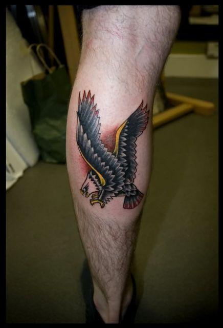Tatuagem pequena na panturrilha do desenho de uma águia em posição de ataque