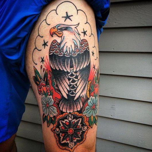 Tatuagem muito colorida de uma águia vista de costas com flores ao seu redor e uma bússola antiga abaixo dela