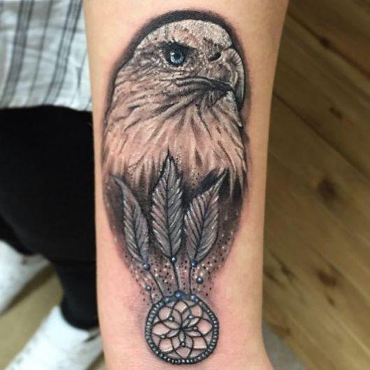Tatuagem da cabeça de uma águia olhando para o horizonte com um apanhador de sonho onde seria seu peito