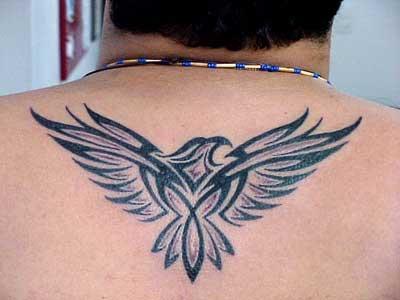 Tatuagem tribal de uma águia com as asas abertas feita na parte superior das costas de um homem